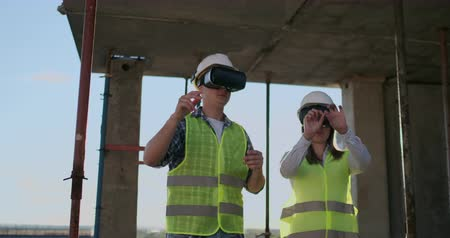 ev idaresi : Two contemporary crew workers using VR to visualize projects standing in unfinished building on construction site, copy space. Stok Video