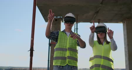 инспектор : A man and a woman engineers at a construction site in VR glasses manage the construction of a building discussing a development plan.