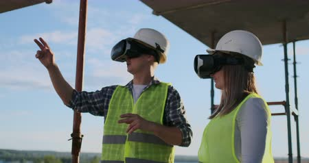 obnovitelný : Two contemporary crew workers using VR to visualize projects standing in unfinished building on construction site, copy space. Dostupné videozáznamy