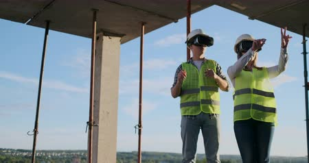 прораб : Waist up portrait of two modern construction workers using VR gear to visualize projects on site, copy space.
