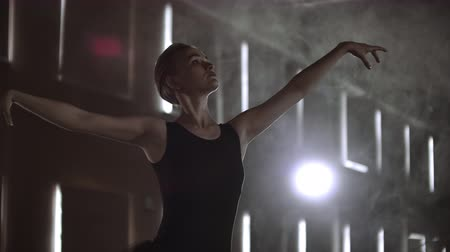 scenes : Slow motion: Diligent young graceful ballerina dancing elements of classical ballet in the dark with light and smoke on the background. Beautiful young ballerina in darkness