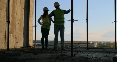 inspektor : Construction Business : teamwork concept : Young engineer standing behind looking at a building site, wearing a safety helmet.