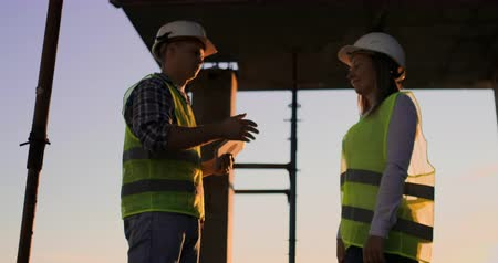 investidor : Builders man with a tablet and a woman in white helmets shake hands at sunset standing on the roof of the building.