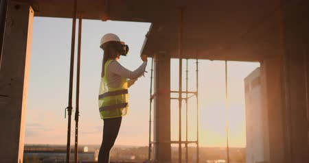 inspektor : A woman engineer at a construction site in virtual reality glasses moves her hands simulating the work of the interface of the future innovative control of the construction of buildings. Dostupné videozáznamy