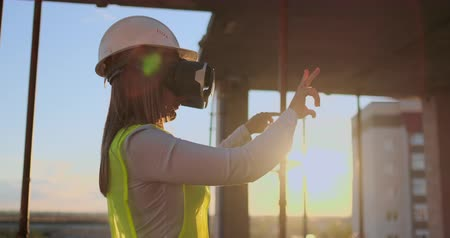 mais : Woman expert engineer Builder in VR glasses and helmet checks the progress of skyscraper construction moving his hands at sunset visualizing the building plan.