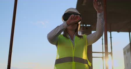 female measurements : Woman inspector in VR glasses and helmet checks the progress of the construction of a skyscraper moving his hands at sunset visualizing the plan of the building. Stock Footage