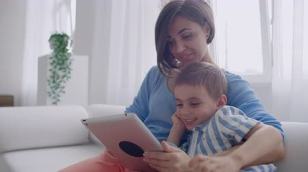 interiér : Mother And Son Using Tablet Looking At Screen And Talking On Sofa In Cozy House.