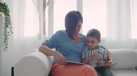alfabetização : Mother and son read books. Happy young mother and son read books on the sofa at home.
