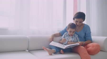 magasine : Happy mother and child son reading book laughing in bed. Happy family mother and child son reading holding book lying in bed, smiling mom baby sitter.