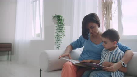 gramotnost : Mother Sitting With Son Reading Story Indoors.