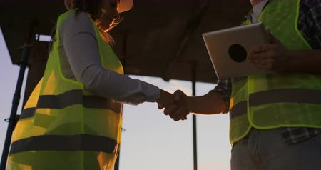 inspektor : Builder man with a tablet and a woman inspector in white helmets shake hands at sunset standing on the roof of the building. Symbol of agreement of successful work.
