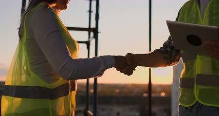inspektor : Builders man with a tablet and a woman in white helmets shake hands at sunset standing on the roof of the building.