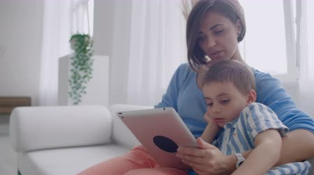 bağ : Mother and son playing with digital tablet at home. Young mother with her 5 years old smiling with digital tablet at home. Stok Video