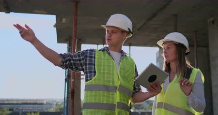 сороковые годы : Construction site Team or architect and builder or worker with helmets discuss on a scaffold construction plan or blueprint or checklist.