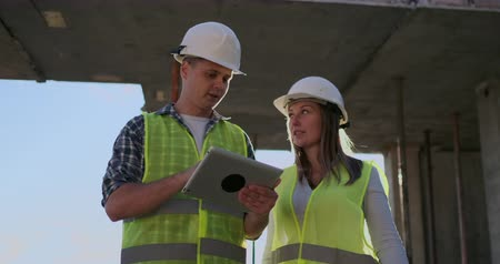 ビルダー : Two engineers a man and a woman with a tablet computer at a construction site condemn the construction plan of the building