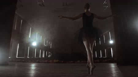 тапочка : Slow motion: the prima ballerina in a black dress performs rotations and graceful dance moves. The camera moves on gimbal.