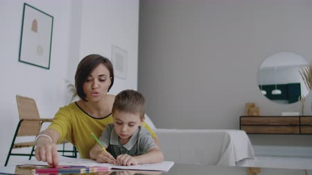kleurplaten : Mother in yellow jacket and son in t-shirt sit at the table and draw together color pencils on paper. Happy childhood. Loving helps his son in pre-school training and develops creativity in the child.