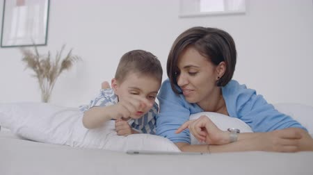 мультфильмы : Mom and son looking at the tablet screen lying on a white bed. Play games with your son on your tablet computer and watch funny videos Стоковые видеозаписи