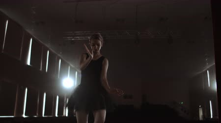 初演 : SLOW MOTION: Ballerina dancing in Pointe shoes on stage in smoke in the dark light back view. the camera moves on gimbal.
