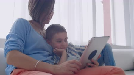 ebook : Mother and son playing with digital tablet at home. Young mother with her 5 years old smiling with digital tablet at home. Stock Footage