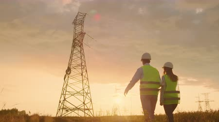 mérnök : The view from the back: Two engineers, a man and a woman in helmets with a tablet of engineer walk on field with electricity towers and discuss the further construction of towers.