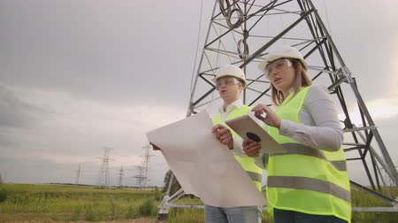 transzformátor : Coworking engineers with tablets on solar plant. Adult men and women in hardhats using tablets while standing outdoors on transformer platform. Transportation of clean energy