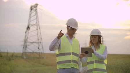 inspector : Coworking engineers with tablets on solar plant. Adult men and women in hardhats using tablets while standing outdoors on transformer platform. Transportation of clean energy
