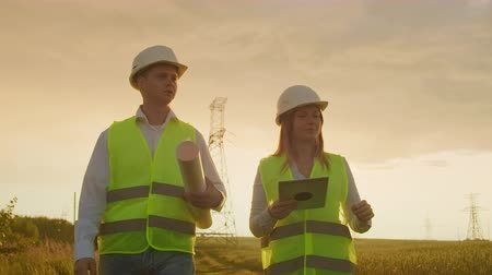 инспектор : Coworking engineers with tablets on solar plant. Adult men and women in hardhats using tablets while standing outdoors on transformer platform. Transportation of clean energy