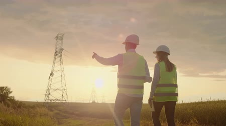 haute tension : The view from the back: Two engineers, a man and a woman in helmets with a tablet of engineer walk on field with electricity towers and discuss the further construction of towers.