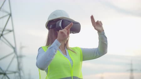 watt : A woman electrician in virtual reality glasses moves her hand simulating the work with the graphical interface of a power plant against the background of high-voltage electric transmission lines Stok Video