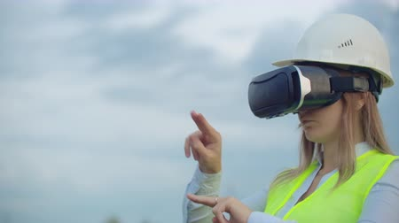 visão global : High-voltage power lines controlled by a female engineer using virtual reality to control power. Alternative energy sources in a modern city.