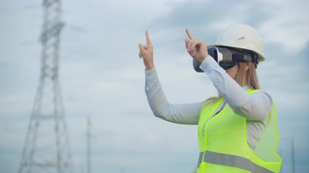 inspektor : A woman electrician in virtual reality glasses moves her hand simulating the work with the graphical interface of a power plant against the background of high-voltage electric transmission lines Dostupné videozáznamy