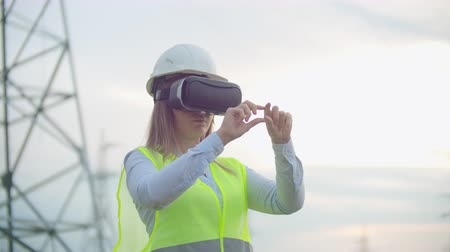 watt : High-voltage power lines controlled by a female engineer using virtual reality to control power. Alternative energy sources in a modern city.