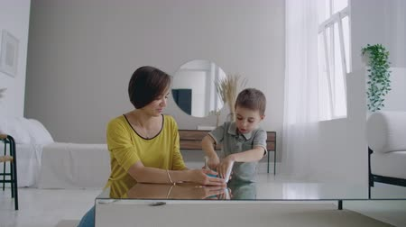 puericultura : Happy and laughing mom and son play together with a Lizun, a liquid stretchable toy Stock Footage