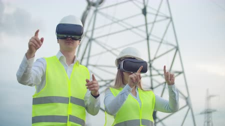 visão global : Two engineers of power engineers in VR glasses move their hands simulating the operation of the interface of the control system