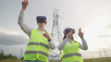 cabling : High-voltage power lines under the control of two engineers using virtual reality to control power. Alternative energy sources in a modern city Stock Footage
