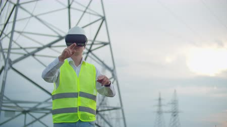 inspektor : Portrait of a modern man of the Comptroller of the engineer conducting the inspection via virtual reality glasses and a white helmet, dressed in uniform in the background the towers of power