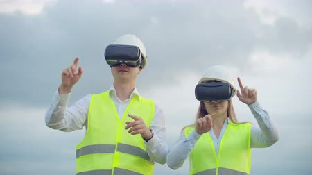 percepção : A man and a woman engineer in VR glasses control the power distribution of electric networks and the delivery of electricity against the background of electric towers with high-voltage cables.