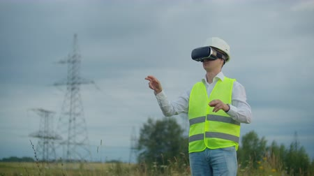 watt : High-voltage power lines controlled by a male engineer using virtual reality to control power. Alternative energy sources in a modern city.