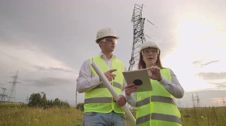 cabling : Two electricians work together, standing in the field near electricity transmission line in helmets. Standing in the field near with power transmission