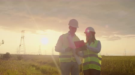 inspektor : Coworking engineers with tablets on solar plant. Adult men and women in hardhats using tablets while standing outdoors on transformer platform. Transportation of clean energy