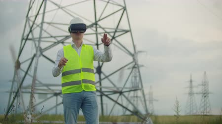 haute tension : A male electrician in virtual reality glasses moves his hand simulating the work with the graphical interface of the power plant against the background of high-voltage electric transmission lines