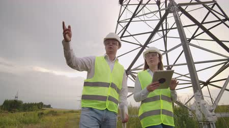 electrici�«n : Two electricians work together, standing in the field near electricity transmission line in helmets. Standing in the field near with power transmission