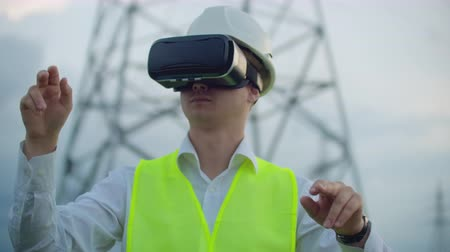 percepção : Middle plan male energy engineer in virtual reality glasses and white helmet on the background of high-voltage power line towers Stock Footage