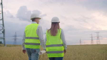 передавать : Back two the Engineer and the controller with a tablet PC and the drawings are about lines and transmission towers and discuss the expansion plan and transportation energy for towns and cities