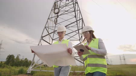 передавать : Engineer and supervisor with tablet PC and the drawings are about lines and transmission towers and discuss the expansion plan and transportation energy for towns and cities.