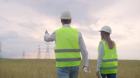 felülnézet : The view from the back: group of engineers at a high-voltage power plant with a tablet and drawings walk and discuss a plan for the supply of electricity to the city.