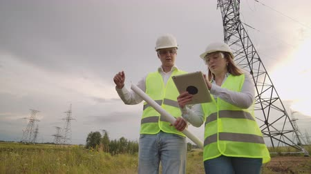 inspektor : Engineer and supervisor with tablet PC and the drawings are about lines and transmission towers and discuss the expansion plan and transportation energy for towns and cities.