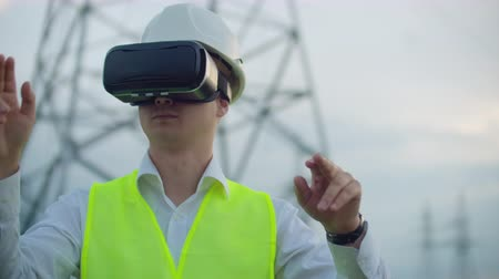 working together : High-voltage power lines controlled by a male engineer using virtual reality to control power. Alternative energy sources in a modern city.