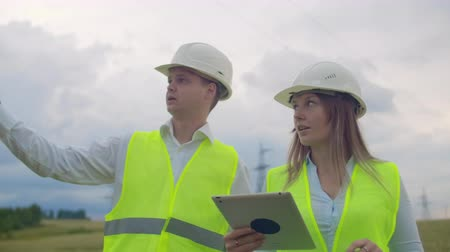 ostříhané : Power lines, man and woman engineers with a tablet in their hands check the progress of the installation of new towers and analyze the network.
